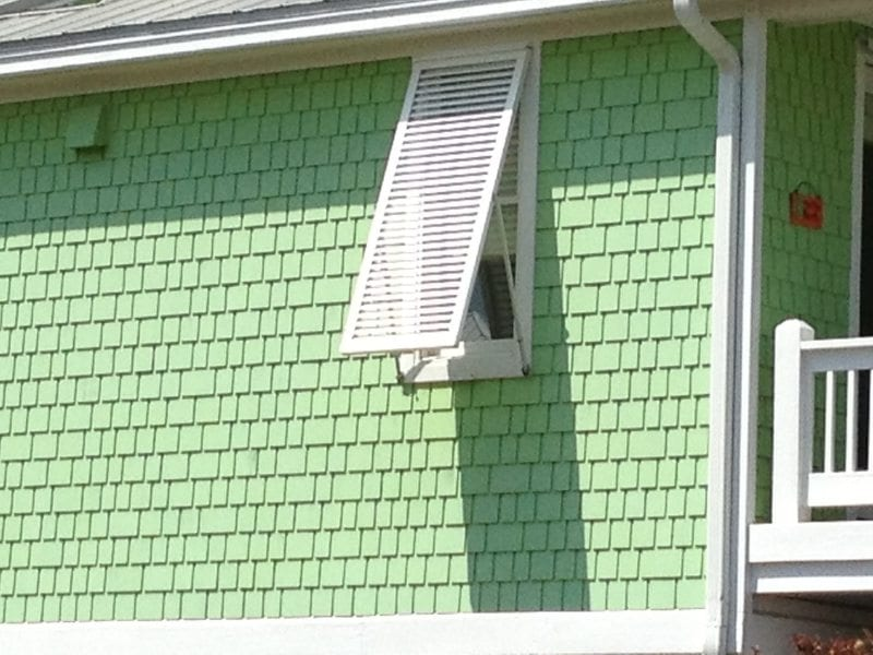 Closeup View of Bahama Shutters for Hurricane Protection on the Side of a Yellow House Near Carolina Beach