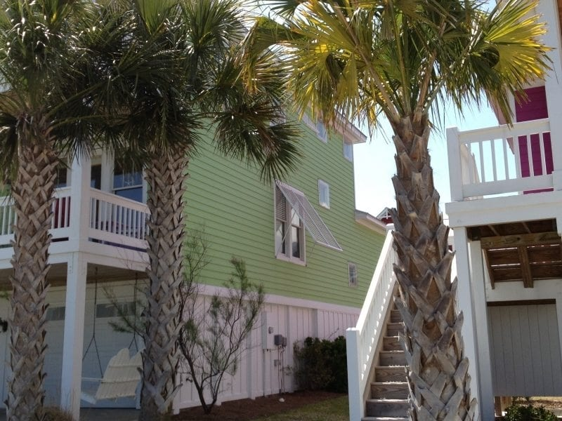 Bahama Shutters for Hurricane Protection on the Side of a Yellow House, with Foliage near Carolina Beach