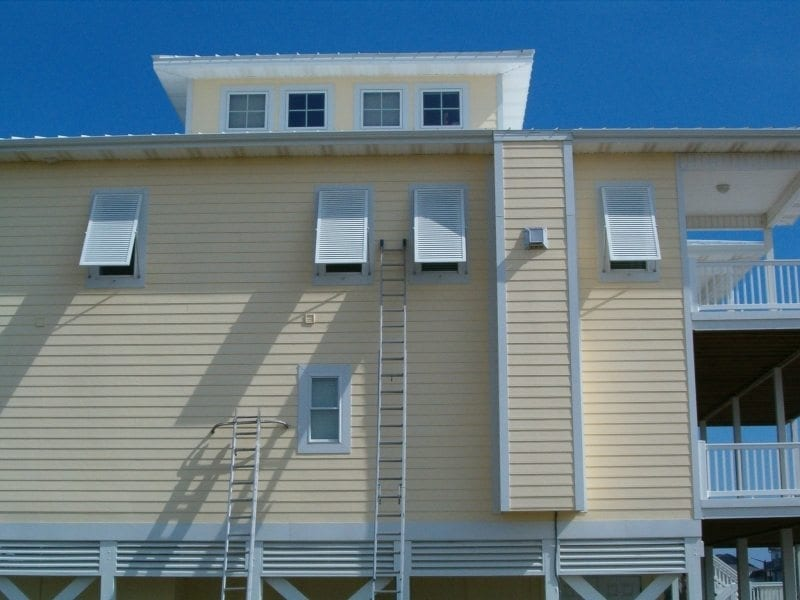 Panel Shutters for Hurricane Protection on the Back of a Yellow House Near Carolina Beach